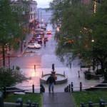 pedestrains walk around a fountain in a rainy streetscape